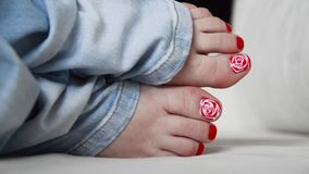 Female feet with red lacquer on nails on couch stock video