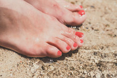 Female feet with red pedicure in beach sand Royalty Free Stock Images