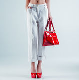 Female feet in red shoes and bag. Beautiful female feet in red shoes and bag Royalty Free Stock Photography