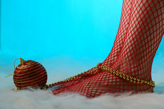 Female feet in red stockings wrapped with gold beads Royalty Free Stock Photography