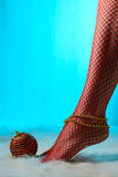 Female feet in red stockings wrapped with gold beads Royalty Free Stock Images