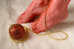 Female feet in red stockings wrapped with gold beads Royalty Free Stock Photo
