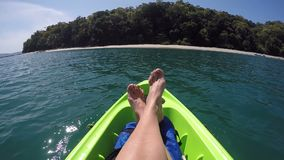 Female feet relaxing on kayak sailing in pacific ocean point of view pov, inspirational landscape, active adventure