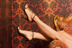 Female feet in sandals are on chair Royalty Free Stock Photography