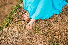 Female feet in sandals. On dry grass. A girl in a blue sarafan Stock Image