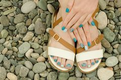 Female feet in sandals and hands with a blue manicure on pebbles. Top view Royalty Free Stock Image