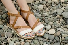 Female feet in sandals, pebbles, close-up.  Royalty Free Stock Photos