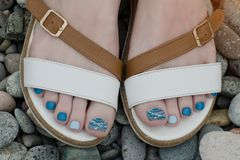 Female feet in sandals, pebbles, close-up.  Royalty Free Stock Images
