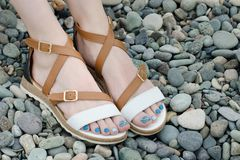 Female feet in sandals, pebbles, close-up.  Stock Photography