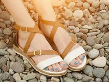 Female feet in sandals, pebbles, close-up.  Stock Photo