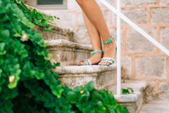 Female feet in sandals. On the stone steps. A girl in a blue sar Royalty Free Stock Image
