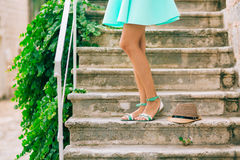 Female feet in sandals. On the stone steps. A girl in a blue sar Royalty Free Stock Photography