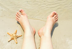 Female feet on a sandy beach Royalty Free Stock Images