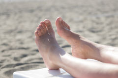 Female feet on the sandy beach Stock Photos