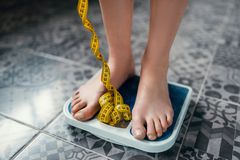 Female feet on the scales closeup, measuring tape. Fat or calories burning concept. Weight loss, hard dieting Royalty Free Stock Photo