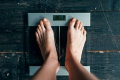 Female feet on the scales with inscription help. Female feet on the scales with the inscription help. Fat or calories burning concept. Weight loss, hard dieting Royalty Free Stock Image