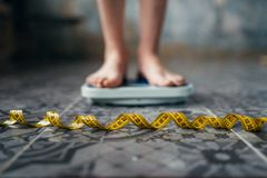 Female feet on the scales, measuring tape. Fat or calories burning concept. Weight loss, hard dieting Royalty Free Stock Images