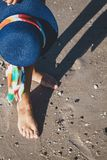 Female feet on the sea beach. Female feet in waves of the sea and hat on summer sunny beach Royalty Free Stock Photos