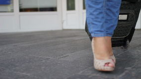 Female feet in shoes and jeans walking with travel suitcase. Close up. Women in beige shoes and blue jeans with a suitcase walking by camera stock video footage