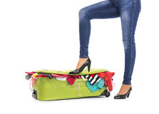 Female feet in shoes on a suitcase. Stock Photo
