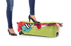 Female feet in shoes on a suitcase. Stock Image