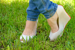 Female feet in shoes with wedge heels on green grass Stock Images