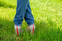 Female feet in shoes with wedge heels on green grass Royalty Free Stock Photography