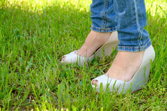 Female feet in shoes with wedge heels on green grass. Woman's feet in shoes with wedge heels on green grass Stock Photography