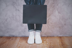 Female feet with shopping bag. On concrete background. Mock up Stock Photos