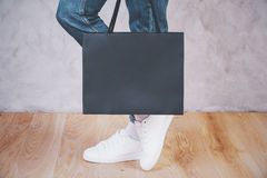 Female feet shopping bag side. Sideview of female feet with shopping bag on concrete background. Mock up Stock Image