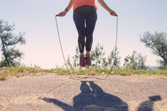 Female feet in sneakers jumping on a skipping rope. In summer Royalty Free Stock Image