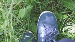 Female feet in sneakers walks on the green grass in slow motion. 1920x1080. Hd stock video