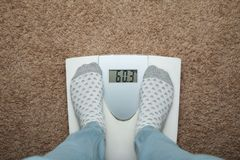 Female feet in socks on electronic scales. Excess weight and diet royalty free stock image