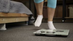 Female feet in socks standing on weight scale stock footage