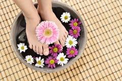 Female feet at spa salon on pedicure procedure Stock Photos