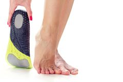 Feet and orthopedic insole. Female feet stand on their toes and orthopedic insole in the hand Stock Photos