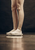 Female feet standing on bathroom scales Stock Photography
