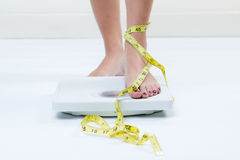 Female feet standing on a bathroom scales and a tape measure Stock Photo