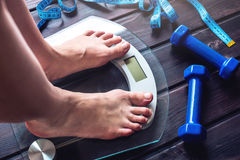 Female feet standing on electronic scales, dumbbells and measuring tape. Concept of slimming and weight loss. Female feet standing on electronic scales for stock photos