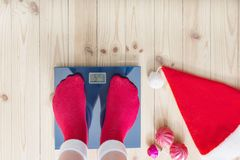 Female feet standing on electronic scales for weight control in. Feet standing on electronic scales for weight control in red socks with Christmas decoration royalty free stock images