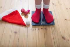 Female feet standing on electronic scales for weight control. In red socks with Christmas decoration stock photos