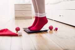 Female feet standing on electronic scales for weight control in. The female feet standing on electronic scales for weight control in red socks with Christmas royalty free stock photo