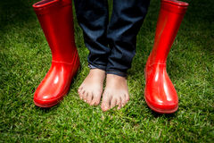 Female feet standing on green grass next to red rain boots. Closeup photo of female feet standing on green grass next to red rain boots Stock Photo