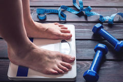 Female feet standing on mechanical scales, dumbbells and measuring tape. Concept of slimming and weight loss. Female feet standing on mechanical scales for stock photography