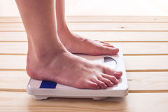 Female feet standing on mechanical scales for weight control on wooden background. Concept of slimming and weight loss Stock Photo