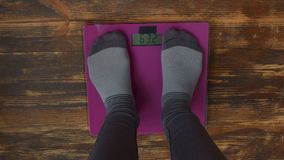 Female feet standing on weight scales stock footage