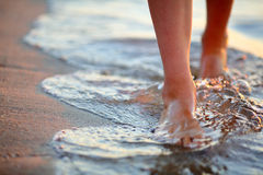 Female feet step on the sea wave. Summer vacations concept royalty free stock images