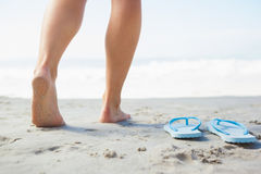 Female feet stepping on sand beside flip flops. On a sunny day stock photos