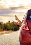 Female feet stick out of car window Stock Images