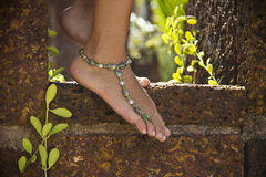 Female feet on stone with bracelet on ankle Royalty Free Stock Photography